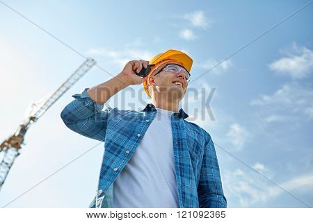 industry, building, technology and people concept - close up of male builder in hardhat with walkie talkie or radio outdoors