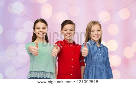 childhood, fashion, gesture and people concept - happy smiling children showing thumbs up over pink holidays lights background