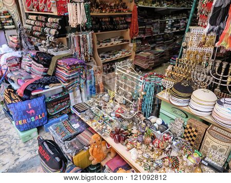 JERUSALEM ISRAEL - JULY 13 2015: Narrow stone street among stalls with traditional souvenirs and goods at bazaar in Old City - popular place among tourists and pilgrims visiting Jerusalem.