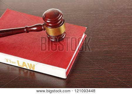 Gavel and book on wooden background