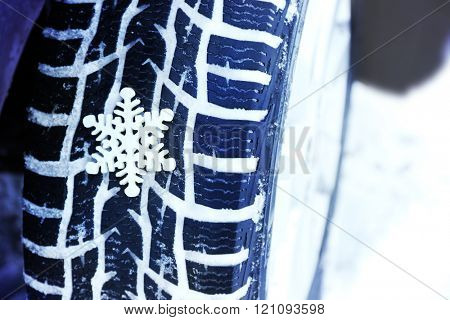 Winter tires in snow with snowflake, closeup