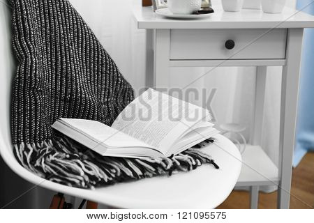 A soft blanket and a book on the chair. Peace and comfort concept