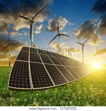 Solar panels with wind turbines in the setting sun. Concept of energy resources.