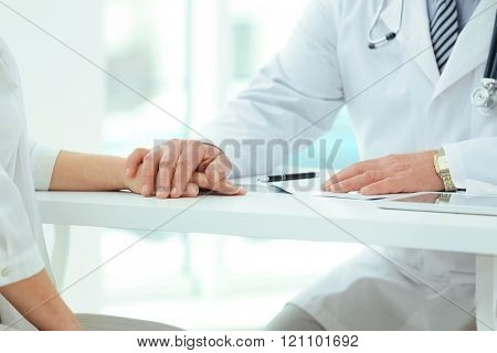 Hands of doctor and patient on table in office
