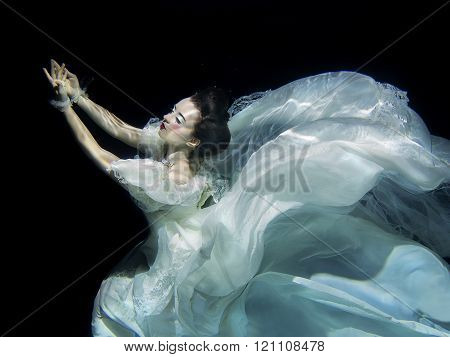 young girl in long white luxury dress underwater on the black background