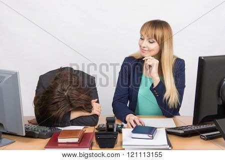 The Situation In Office - Frustrated Woman Lay On The Table, Her Colleague Looking At Her Haughtily