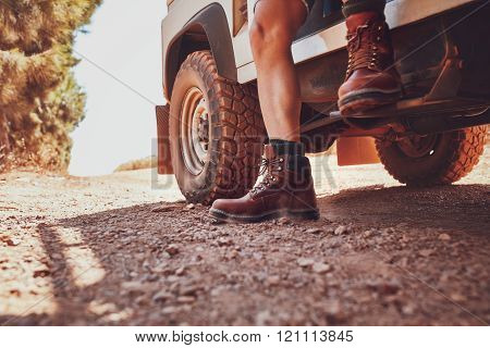 Legs of a man sitting on a off road vehicle.