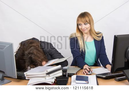 Female Colleagues In The Office, One Had Fallen Asleep On A Pile Of Folders, And The Second Looked A