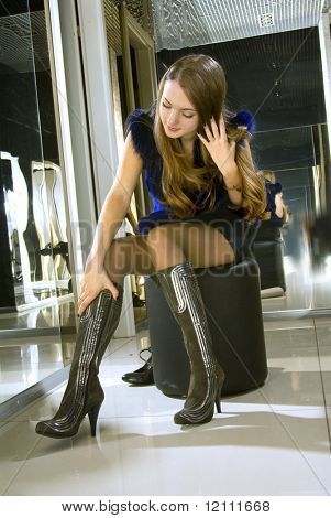 beautiful girl fits on a white boots in a boutique