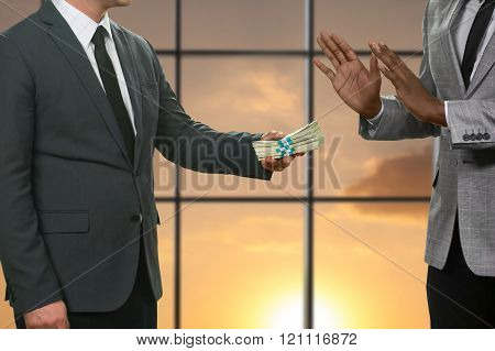 Darkskinned businessman refusing huge money.