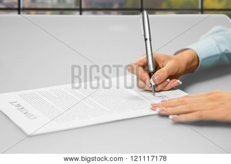 Woman's hands signing office papers.