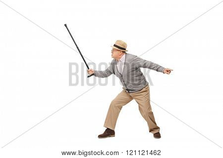 Studio shot of an angry senior man holding his cane as a sword isolated on white background