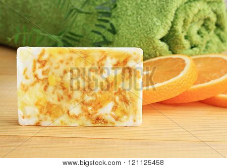 Bar of handmade citrus soap with orange zest.