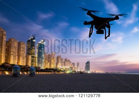 Drone silhouette flying above Dubai city panorama