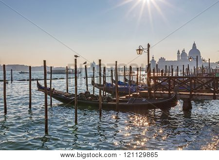 Venice At Dusk. Gondolas At Sunset With Dome Of Santa Maria Della Salute In Background.