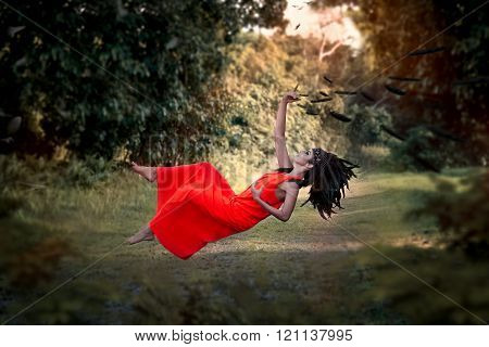 Young woman in red dress and american indian bonnet levitating in the park.