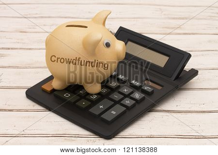 Funding your project A golden piggy bank and calculator on a wood background with text Crowdfunding