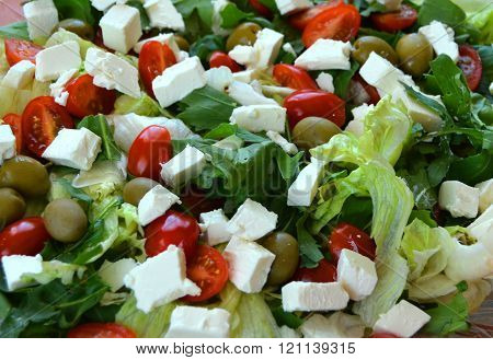 Salad with fresh vegetables. Delicious green salad with tomatoes, olives , cheese and balsamic vinegar