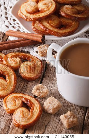 Coffee with milk and cookies Palmiers close-up. Vertical