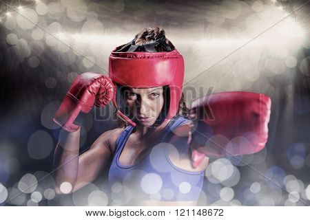 Portrait of female boxer with gloves and headgear against spotlight