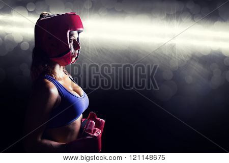 Side view of female boxer with headgear and gloves against spotlight