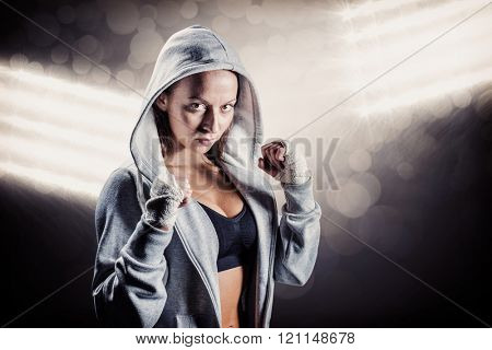 Portrait of female boxer in hood with fighting stance against spotlight