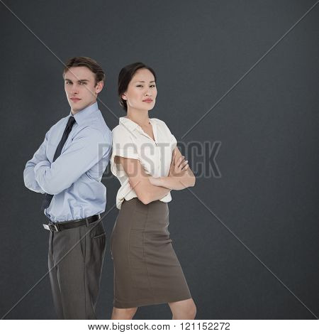 Business colleagues with arms crossed in office against grey background