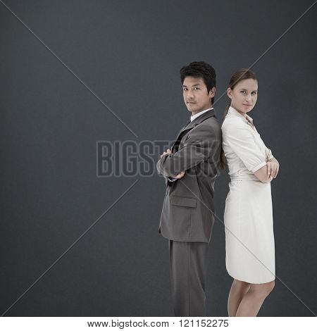 Portrait of business people standing back-to-back against grey background