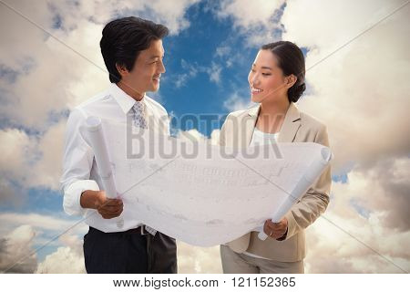 Estate agent looking at blueprint with potential buyer against blue sky with white clouds