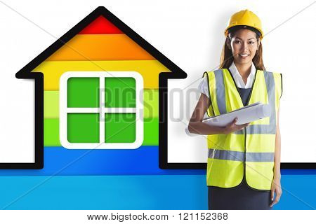 Architect woman with yellow helmet and plans against colorful house on white background