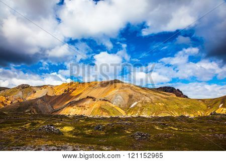 Multi-colored rhyolite mountains - orange, yellow, green and blue. Travel to Iceland in July, volcanic summer tundra