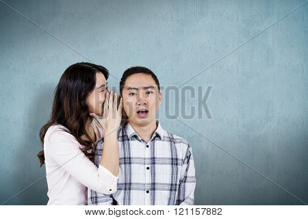 Woman whispering secret to husband against blue background