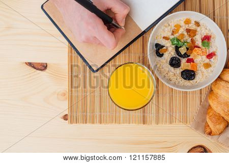 Top view of healthy breakfast and hand writing in notebook on the table