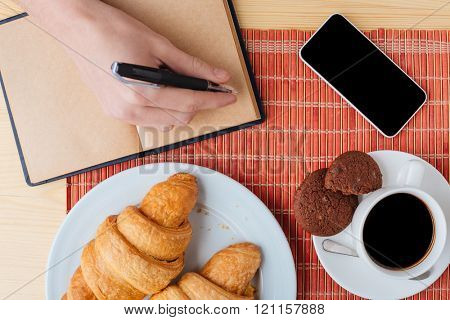 Top view of table with breakfast, cell phone and notebook