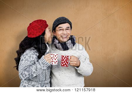Older asian couple having hot drinks against orange background