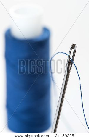 A needle with a wide eye with threaded into it threads. In the background to blur spool of thread.
