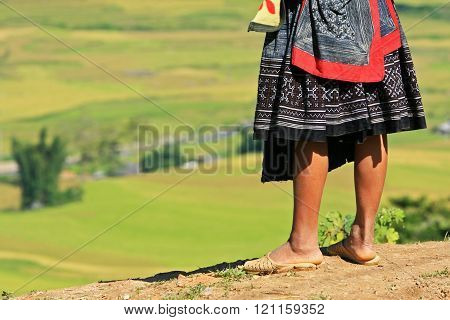 Hmong woman standing on the side of a mountain pass