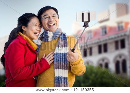 Older asian couple on balcony taking selfie against low angle view of city buildings on sunny day