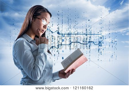 Concentrated businesswoman reading book against digital blue key