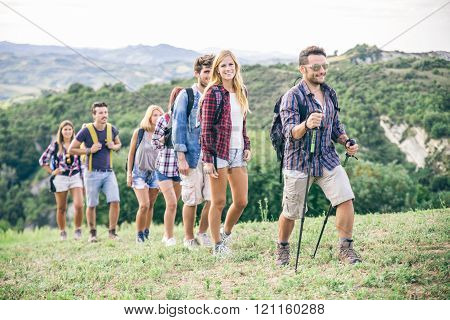 Group of hikers walking in the nature - Friends taking an excursion on a mountain walking in a row
