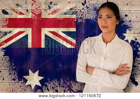 Casual businesswoman with arms crossed against australia flag in grunge effect