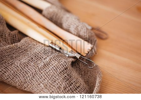 Set of potter sculpting tools lying on wooden table