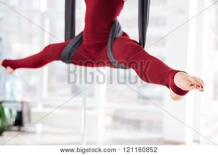 Closeup of legs of young woman doing twine on hammock in aerial yoga studio