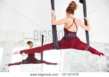 Back view of smiling pretty young woman doing twine using hammock on antigravity youga class