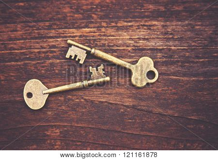 a set of old skeleton keys on a wooden background toned with a retro vintage filter instagram app or action effect
