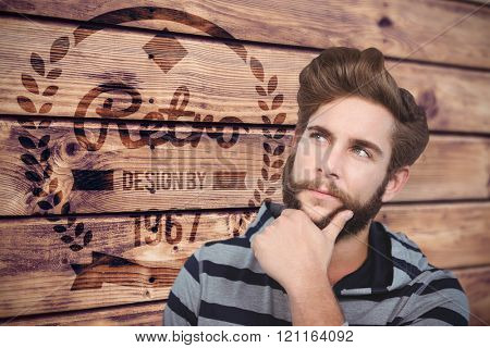 Close-up of thoughtful hipster with hand on chin against wooden planks background