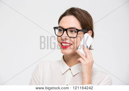 Portrait of happy beautiful business woman in glasses talking on mobile phone over white background