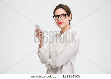 Happy confident young business woman in glasses using smartphone over white background