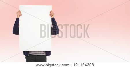 Man showing billboard in front of face against pastel pink