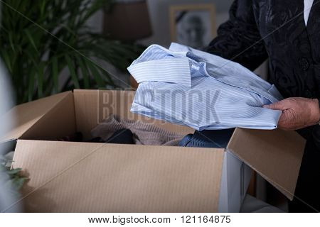 Woman putting clothes into a box